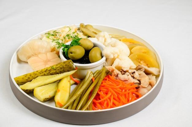 Verschillende soorten ingemaakte groenten op witte achtergrond. ingelegde komkommers, tomatenkers, bladgroente, champignons en knoflook met ui en sla