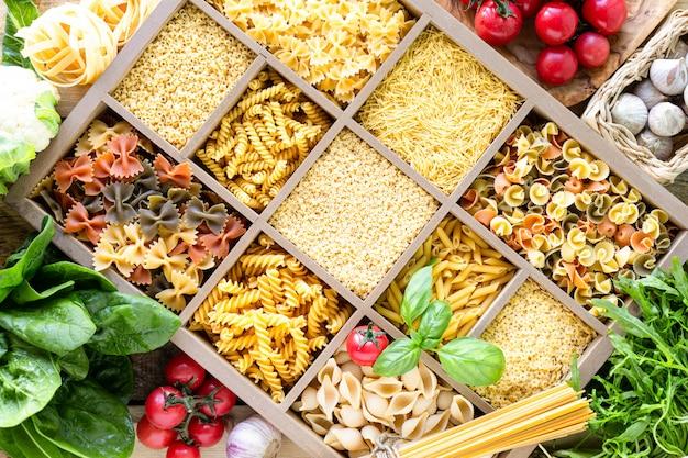 Verschillende soorten italiaanse deegwaren in houten kist, volkoren pasta, pasta, spaghetti, noedels, tagliatelle. bovenaanzicht.