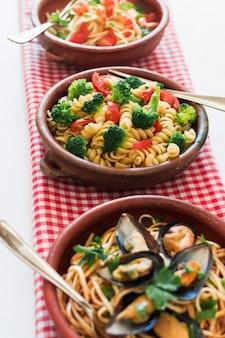 Verschillende soorten italiaanse pasta gerangschikt op geruite servet