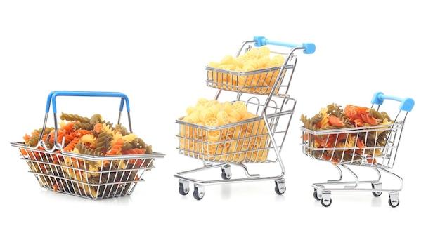 Verschillende soorten italiaanse pasta in een boodschappenmandje van de markt op een wit oppervlak. meelproducten en voedsel bij het koken