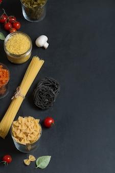 Verschillende soorten italiaanse pasta met groenten op het donkere bord