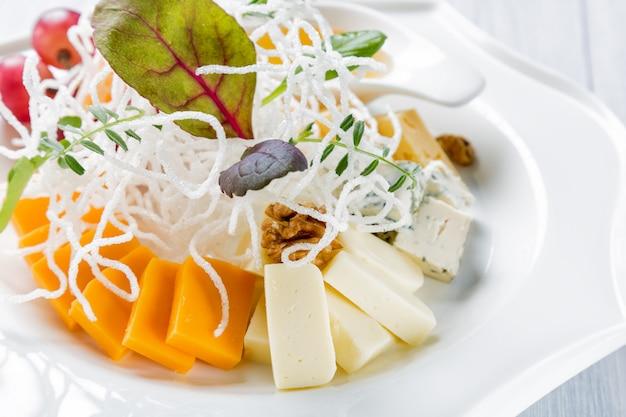 Verschillende soorten kaas met druiven en walnoot op witte plaat