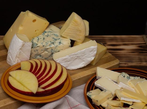 Verschillende soorten kaas op een rustieke houten snijplank met gesneden appel op een donkere achtergrond.