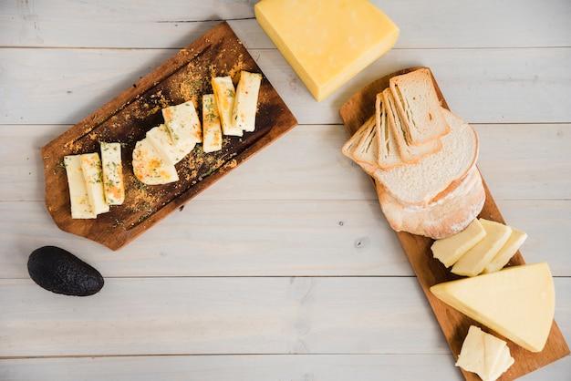 Verschillende soorten kaas plakjes gerangschikt op houten dienblad met avocado op het bureau
