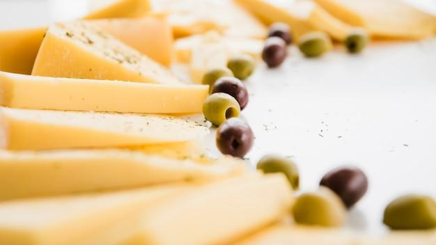 Verschillende soorten kaas plakjes met olijven op witte achtergrond