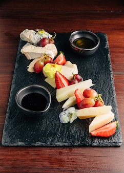 Verschillende soorten kaasdelen (blauwe kaas, brie cheese, cheddar-kaas) geserveerd met honing en wat fruit zoals aardbei en druif.