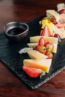 Verschillende soorten kaasdelen (blauwe kaas, brie cheese, cheddar-kaas) geserveerd met honing en wat fruit.