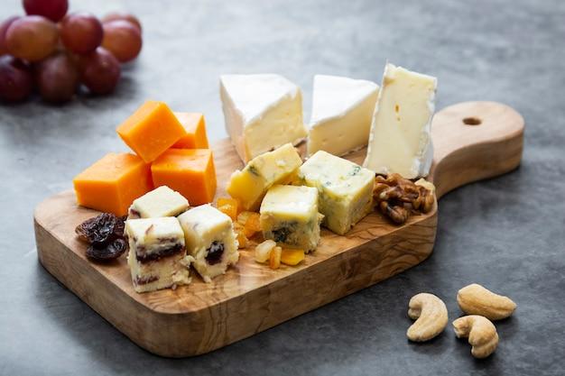 Verschillende soorten kaasplakken, kaasmix op houten snijplank.