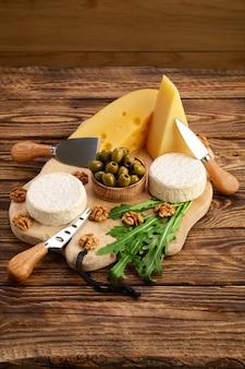 Verschillende soorten kazen - brie, camembert, parmezaanse kaas en gouda op een houten bord met kaasmessen