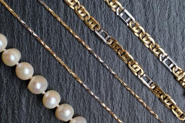 Verschillende soorten kettingen van goud en parels op een stenen bord.