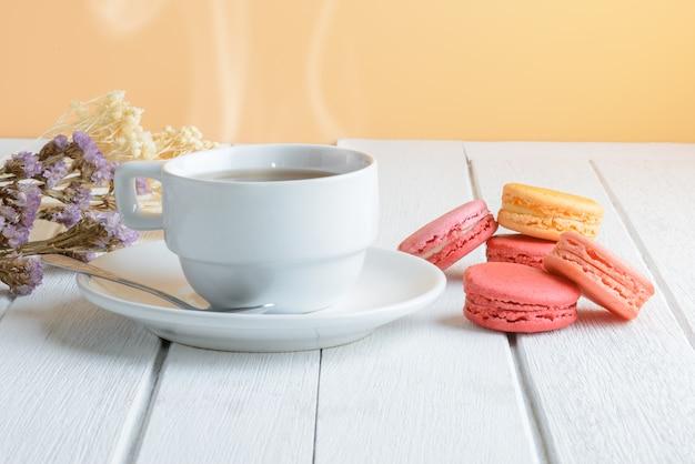 Verschillende soorten kleur van bitterkoekjes met kop warme thee op witte houten oppervlak