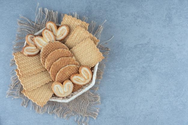 Verschillende soorten koekjes en wafels in mand op zak over grijze tafel.
