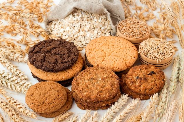 Verschillende soorten koekjes tussen de oren van tarwe en haver op een witte tafel