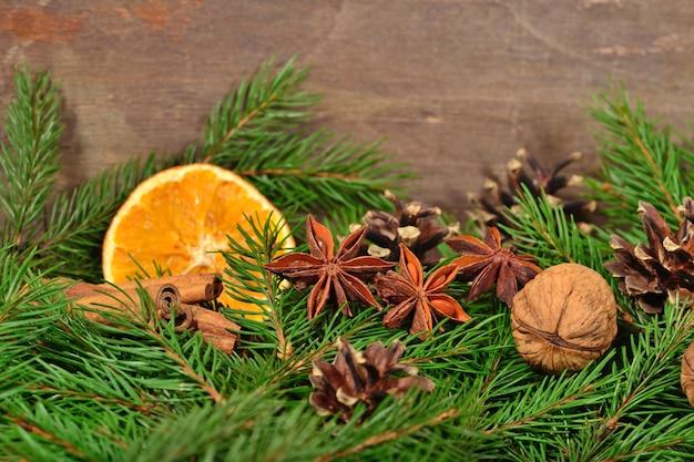 Verschillende soorten kruiden noten gedroogde sinaasappelen en spruse tak op een houten achtergrond