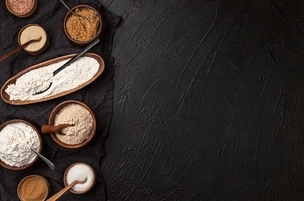 Verschillende soorten meel in houten kommen op zwarte tafel, bovenaanzicht van bloem en deegroller met kopie ruimte