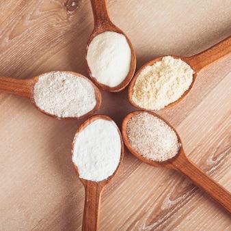 Verschillende soorten meel in vijf houten lepels