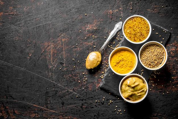Verschillende soorten mosterd op een stenen bord met een lepel. op donkere rustieke tafel