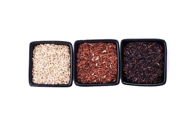 Verschillende soorten niet-witte rijst in zwarte kommen geïsoleerd op wit