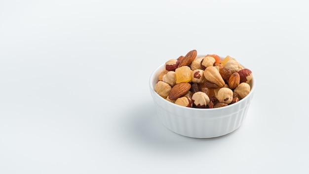Verschillende soorten noten en gedroogde vruchten in een witte kop op een witte achtergrond.
