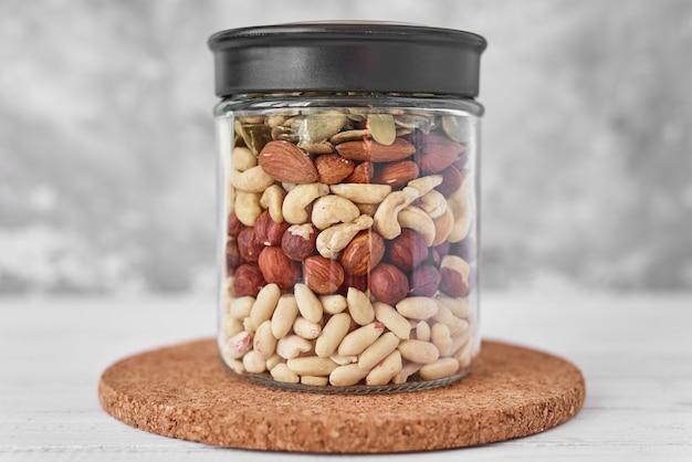 Verschillende soorten noten en zaden in een glazen pot close-up