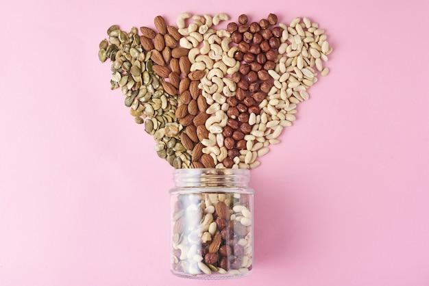 Verschillende soorten noten en zaden in een glazen pot op roze achtergrond, bovenaanzicht