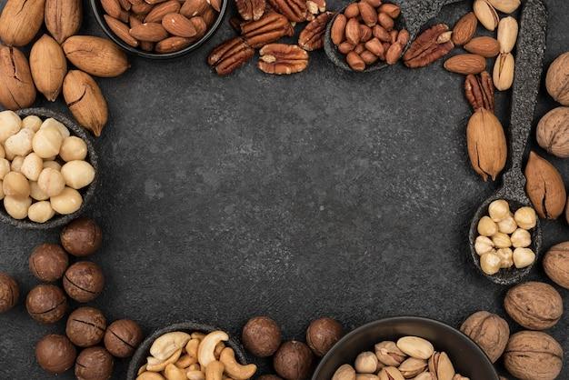 Verschillende soorten noten frame op donkere kopie ruimte achtergrond