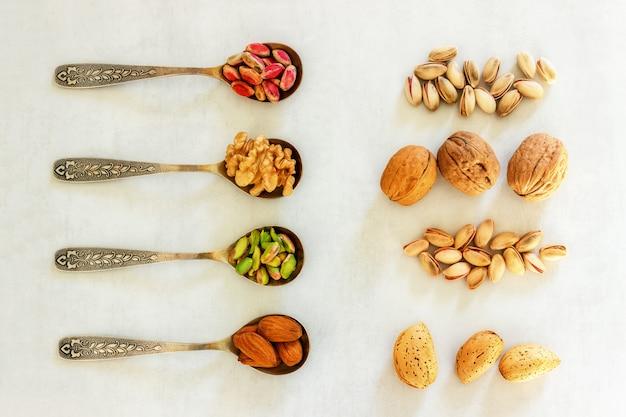 Verschillende soorten noten liggen in lepels