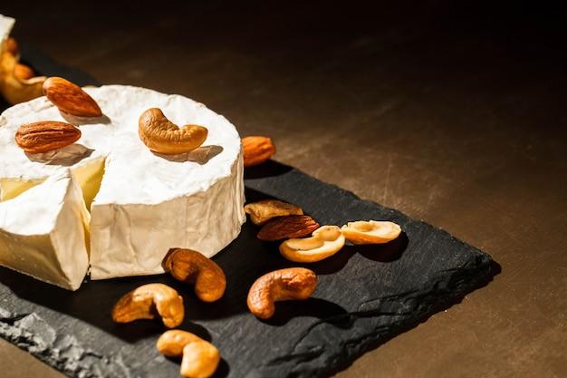 Verschillende soorten noten liggen op brie kaas op zwarte schotel