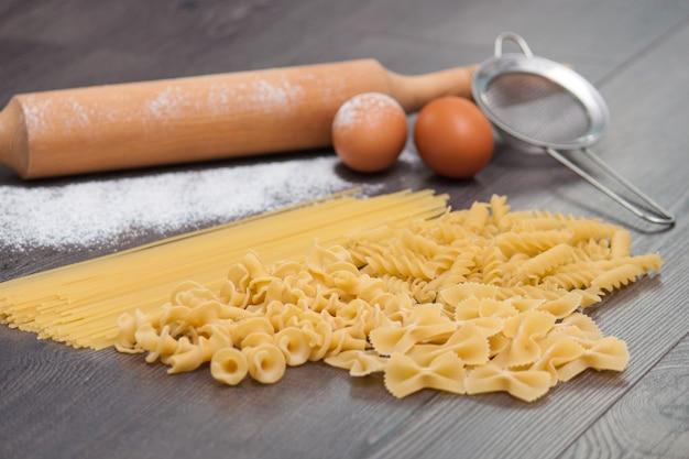 Verschillende soorten of ruwe italiaanse pasta op de houten achtergrond en ingrediënten voor pasta ei