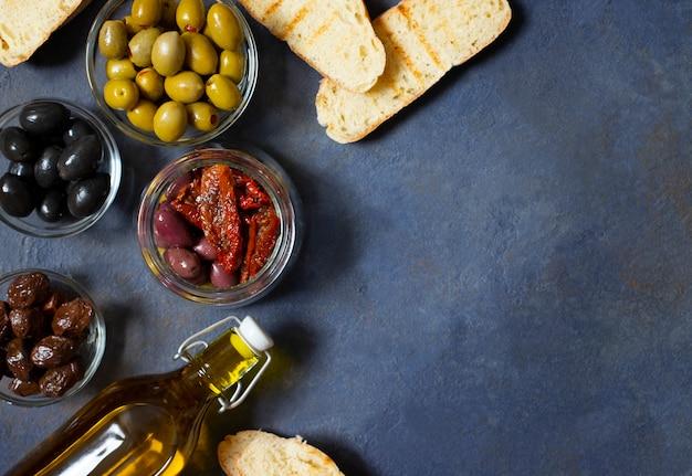 Verschillende soorten olijven, bruschetta, zongedroogde tomaten en olijfolie. mediterrane snacks. bovenaanzicht