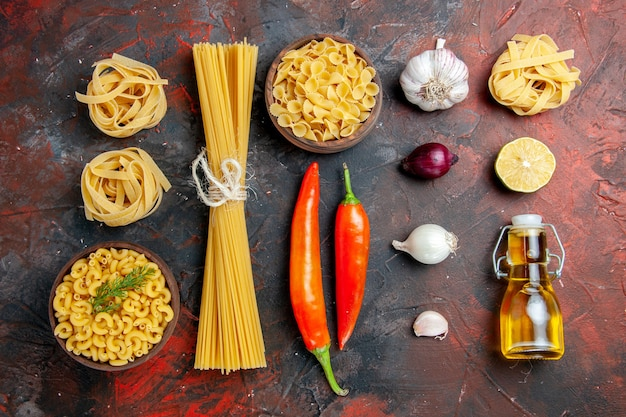 Verschillende soorten ongekookte pasta's en paprika's olie fles knoflook citroen op gemengde kleur achtergrond