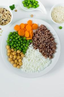 Verschillende soorten pap met groenten op grote plaat met rijstkommen