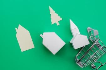 Verschillende soorten papieren huizen; boom die van het het winkelen karretje over groene achtergrond valt