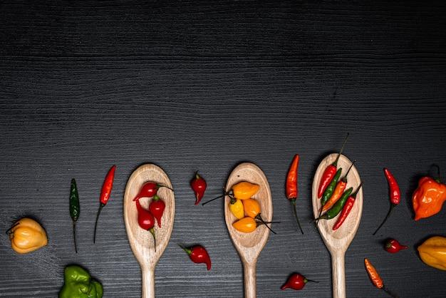 Verschillende soorten paprika's over houten lepels op zwarte rustieke houten achtergrond bovenaanzicht kopieer de ruimte