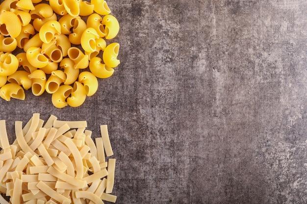 Verschillende soorten pasta aan de linkerkant met kopie ruimte op het grijze stenen oppervlak
