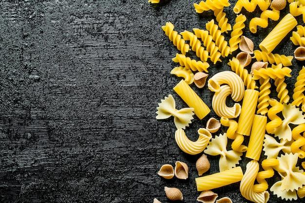 Verschillende soorten pasta drogen op zwarte rustieke tafel.