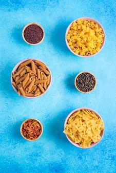 Verschillende soorten pasta in kommen en hete kruiden op blauwe tafel.