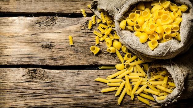 Verschillende soorten pasta in oude zakken op houten achtergrond