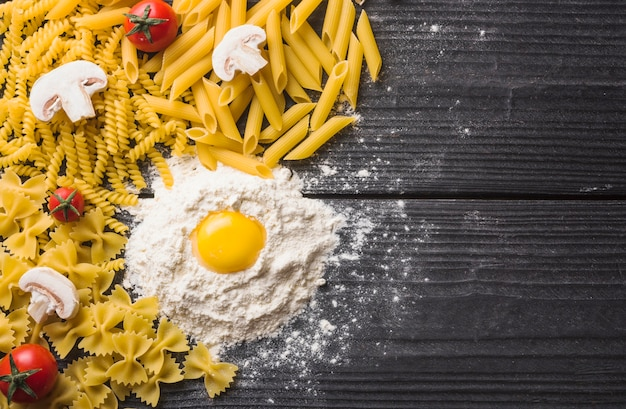 Verschillende soorten pasta met champignons; tomaat en eierdooier op bloem