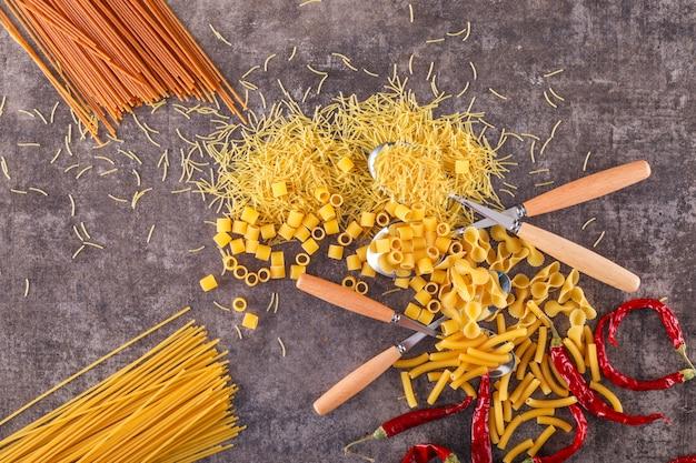 Verschillende soorten pasta met lepels bovenaanzicht