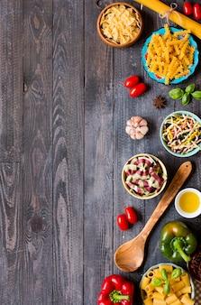 Verschillende soorten pasta met verschillende soorten groenten, gezondheid of vegetarisch concept, bovenaanzicht