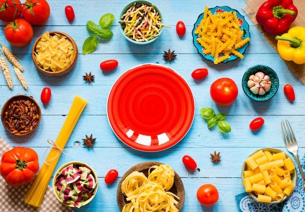 Verschillende soorten pasta met verschillende soorten groenten op een houten tafel