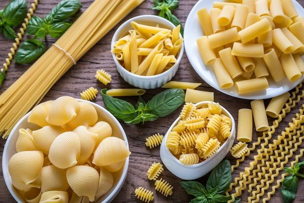 Verschillende soorten pasta op de houten achtergrond