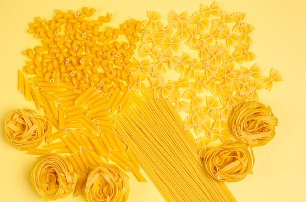Verschillende soorten pasta op een gele achtergrond