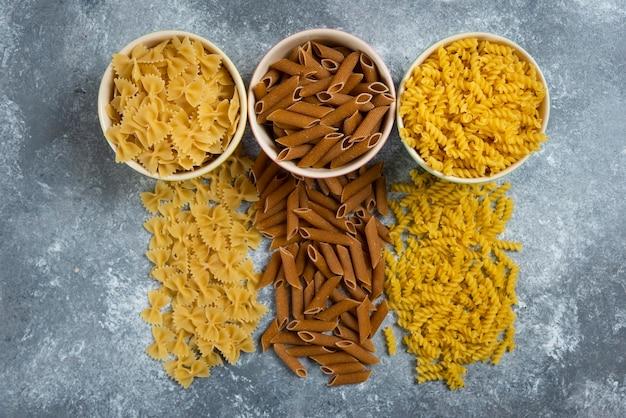 Verschillende soorten pasta op grijs.