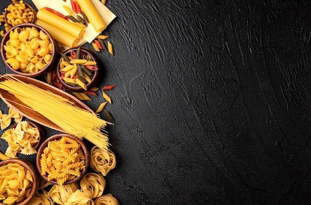 Verschillende soorten pasta op zwarte achtergrond