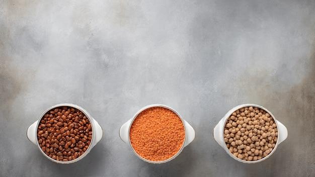 Verschillende soorten peulvruchten: rode bonen, rode linzen, kikkererwten vegetarisch voedsel banner, plaats voor tekst grijs betonnen oppervlak, bovenaanzicht