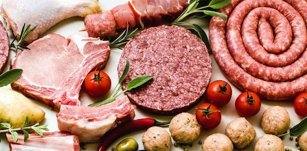 Verschillende soorten rabanner van verschillende soorten rauw vlees: kippendijen, burgers van varkensvlees en rundvlees, ribben en kebabs, gehaktballen van kalkoen