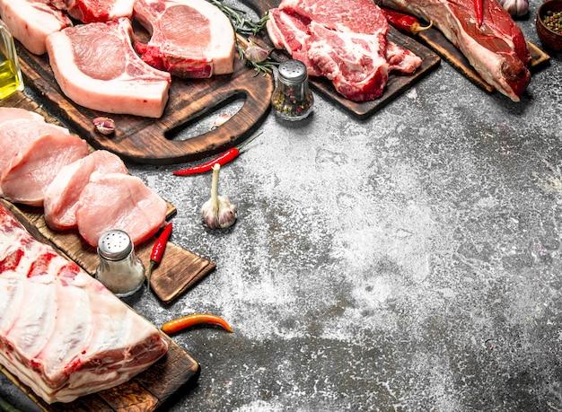 Verschillende soorten rauw varkensvlees en rundvlees met kruiden en specerijen. op rustieke achtergrond.
