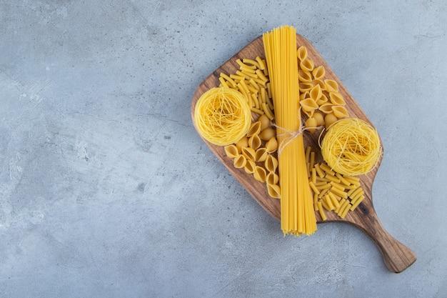 Verschillende soorten rauwe droge pasta op een stenen achtergrond.